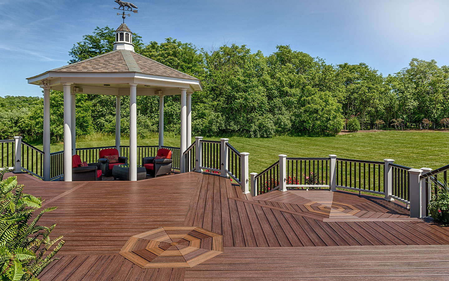 An overlook deck design with a gazebo extends over a lush yard.