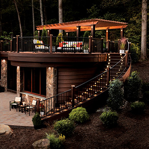 Trex Signature® railing in Charcoal Black complements the vastness of a Transcend deck in Lava Rock and Tiki torch as shown in the Shenandoah Collection